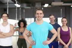 Sportlicher Mann mit Gruppe Athleten in der Turnhalle stockfoto