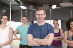Sportlicher Mann mit Gruppe Athleten in der Turnhalle stockfotografie