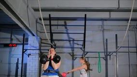 Sportlicher Mann und junge muskulöse Frau, die eine Übung mit Gewichten in der Turnhalle tut stock video