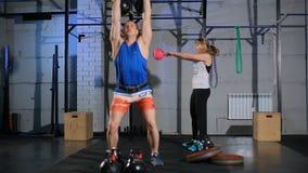 Sportlicher Mann und junge muskulöse Frau, die eine Übung mit Gewichten in der Turnhalle tut stock footage