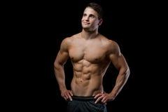 Sportlicher und gesunder muskulöser Mann, der oben auf schwarzem Hintergrund lokalisiert schaut Lizenzfreie Stockbilder