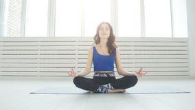 Sportliches übendes Yoga der jungen Frau, sitzend in halber Lotus-Übung, Siddhasana-Haltung, Innen-, Hauptinnenhintergrund stock video