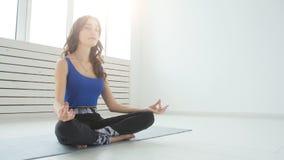Sportliches übendes Yoga der jungen Frau, sitzend in halber Lotus-Übung, Siddhasana-Haltung, Innen-, Hauptinnenhintergrund stock video footage