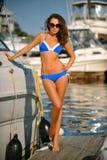 Sportliches Bikinimodell mit dem perfekten Körper, der auf dem Pier steht Lizenzfreie Stockfotos