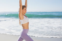 Sportliches blondes Ausdehnen auf den Strand Stockfoto