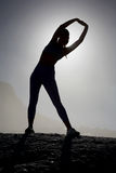Sportliches blondes Ausdehnen auf den Strand auf einem Felsen Stockfoto