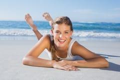 Sportliches blondes Lügen auf dem Strand, der an der Kamera lächelt Stockfoto