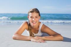 Sportliches blondes Lügen auf dem Strand, der an der Kamera lächelt Lizenzfreie Stockfotos