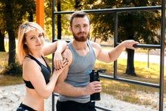 Sportliches blondes Mädchen und bärtiger Mann steht nach Training trai still Lizenzfreies Stockbild