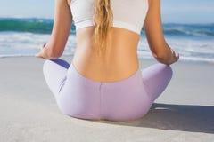 Sportliches blondes Sitzen in der Lotoshaltung auf dem Strand Lizenzfreie Stockfotos