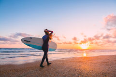 Sportliches Brandungsmädchen gehen zum Surfen Frau mit Surfbrett und Sonnenuntergang oder Sonnenaufgang auf Ozean lizenzfreie stockbilder