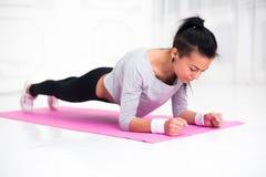 Sportliches geeignetes Abnehmenmädchen, das Plankenübung in der Yogaklasse tut Eignungs-, Ausgangs- und Diätkonzept Stockfoto