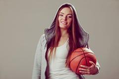 Sportliches jugendlich Mädchen in der Haube, die Basketball hält Stockfoto