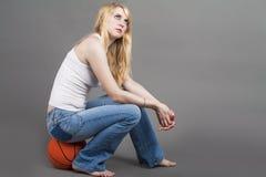 Sportliches kaukasisches blondes weibliches Sitzen auf Basketball-Ball im Bolzen Lizenzfreies Stockfoto