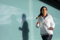 Sportliches Laufen der jungen Frau im Freien Stockfotos
