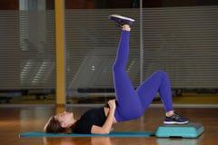 Sportliches Mädchen, das Übung auf Plattform für einen Aerobicschritt tut Lizenzfreie Stockfotografie