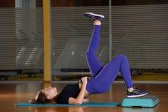 Sportliches Mädchen, das Übung auf Plattform für einen Aerobicschritt tut Lizenzfreies Stockbild