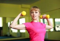 Sportliches Mädchen, das Übung mit Dummköpfen tut Stockfoto