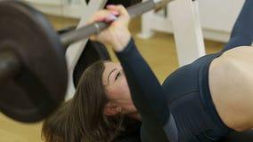 Sportliches Mädchen, das eine Übung mit einer Stange in der nachlässigen Position in der Turnhalle tut stock video