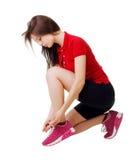 Sportliches Mädchen, das Spitzee binden sitzt Weißer Hintergrund Lizenzfreies Stockbild