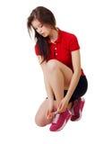 Sportliches Mädchen, das Spitzee binden sitzt Weißer Hintergrund Stockfotografie