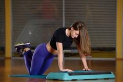 Sportliches Mädchen, das StoßUPS auf Plattform für einen Aerobicschritt tut Stockfotografie