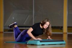 Sportliches Mädchen, das StoßUPS auf Plattform für einen Aerobicschritt tut Lizenzfreie Stockbilder