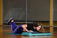 Sportliches Mädchen, das StoßUPS auf Plattform für einen Aerobicschritt tut Stockfoto