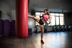Sportliches Mädchen in den Boxhandschuhen hat seinen Fuß auf Tasche Stockfotos
