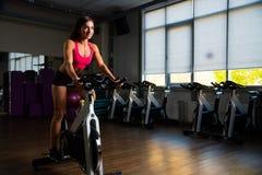 Sportliches Mädchen in der Eignungshalle auf Zyklus Stockbilder