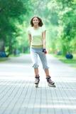 Sportliches Mädchen der Rollschuhlaufen im Park, der auf Inline-Rochen rollerblading ist Stockfotos