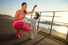 Sportliches Mädchen mit einem Hund im Park lizenzfreie stockfotos
