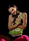 Sportliches Mädchen mit hörender Musik der Kopfhörer auf grauem Hintergrund Junge Frau mit Zopf, trägt grünes T-Shirt, kurze Hose Lizenzfreie Stockfotografie