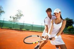 Sportliches Mädchenpraxistennis mit Trainer Lizenzfreie Stockbilder