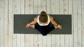Sportliches schönes übendes Yoga der jungen Frau, sitzend in der queren mit Beinen versehenen Position lizenzfreie stockbilder