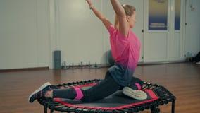 Sportliches Sitz-Mädchen tut, Übungen am Eignungs-Training in der Turnhalle ausdehnend stock video