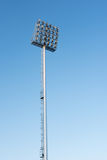 Sportlights tower with blue sky background. In stadium Royalty Free Stock Photo