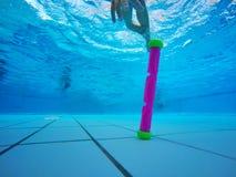 Sportlilla flickan dyker till botten av pölen och samlar leksaker på en blå bakgrund Skjuta under vatten fotografering för bildbyråer