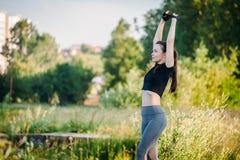 Sportmädchen, das Aufwärmen vor der Ausbildung im Parksommer tut stockbild