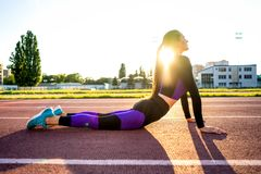 Sportmädchen engagierte sich Yoga in einem Aufwärmen am Stadion bei Sonnenuntergang stockfotos