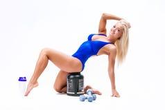 Sportmädchen mit Glas Protein und Dummköpfen lizenzfreie stockbilder