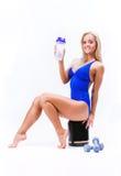 Sportmädchen mit Glas Protein und Dummköpfen lizenzfreie stockfotos