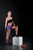 Sportmädchen steht und starrt entlang der Kamera gegen schwarzen Hintergrund an Stockfotografie