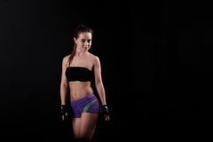 Sportmädchen steht und starrt entlang der Kamera gegen schwarzen Hintergrund an Stockbilder