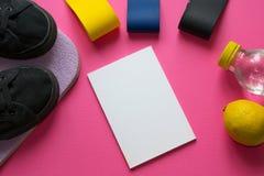 Sportmål Lista av övningar som ska göras Ställ in av färgrika elastiska gummiexpanders, citronen, flaska med vatten, musikband på fotografering för bildbyråer