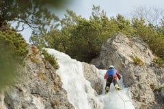 Sportman die aan de winterijs werken die route in openlucht beklimmen stock afbeelding