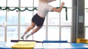 Sportman die op een Trampoline springen en Spleet binnen doen stock videobeelden