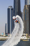 Sportman die stunts op een achtergrond van de torens van de Jachthaven van Doubai in de concurrentie voor de vlieg doen die in Sk stock afbeeldingen
