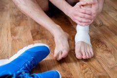 Sportman die zijn verwonde enkel masseren stock foto's