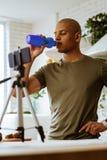 Sportman drinkwater die dorstig na het maken van blog voelen stock foto's